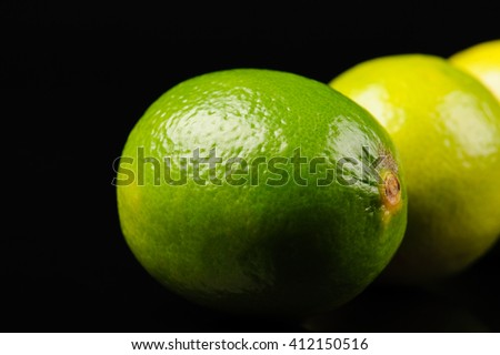 green and yellow lemons on the black background - stock photo