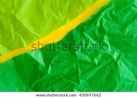 green and yellow wrinkled torn paper - material sample - close up of textured background - stock photo