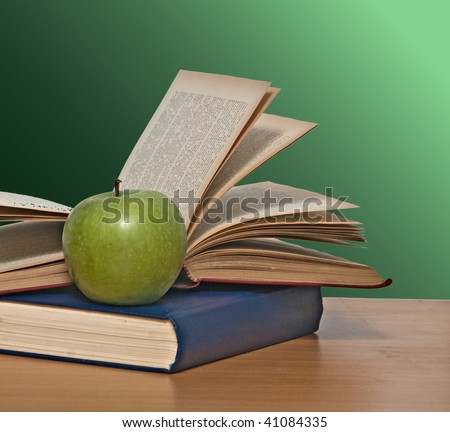Green apple and books on desk