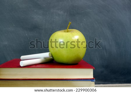 green apple and chalk with blackboard - stock photo