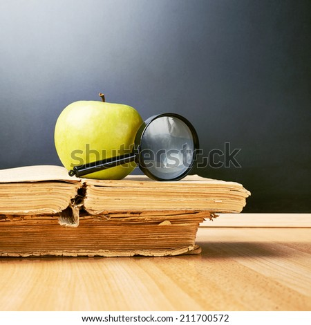Green apple and magnifying glass lying over the opened old books against the blackboard as a back to school composition - stock photo