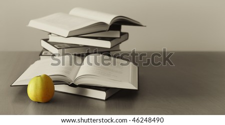 green apple and opened books - stock photo