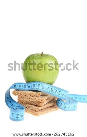 Green apple and rye bread with a blue measuring tape. - stock photo