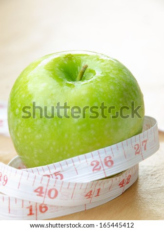 Green apple core and measuring tape. Diet concept - stock photo