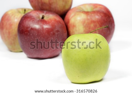 Green apple in front of several red apples
