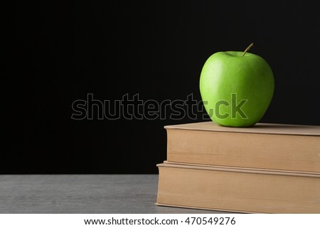 Green apple on old book