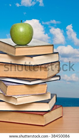 Green apple on pile of books