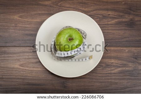 Green apple on plate with tape measure, view from top on wood background - stock photo