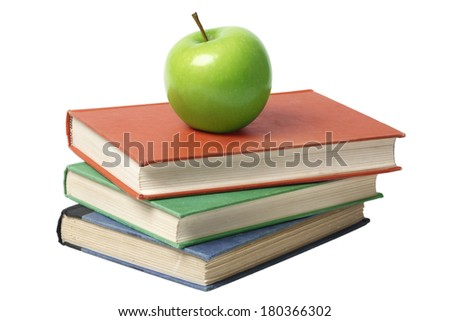 Green apple on top of colorful books on white background