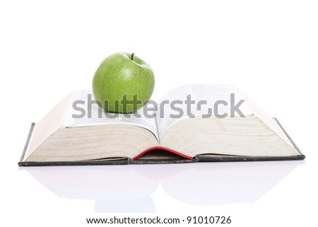 Green apple over a open book isolated on white - stock photo
