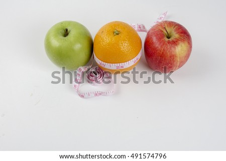 Green apple , red apple , yellow orange  and measuring tape. Diet concept