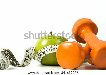 Green apple, tape measure and dumbbells on isolated background. - stock photo