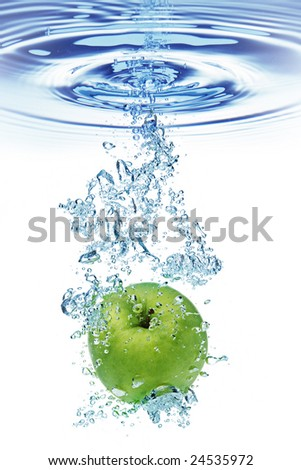 Green apple under water with a trail of transparent bubbles. - stock photo