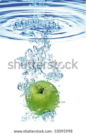 Green apple under water with a trail of transparent bubbles.