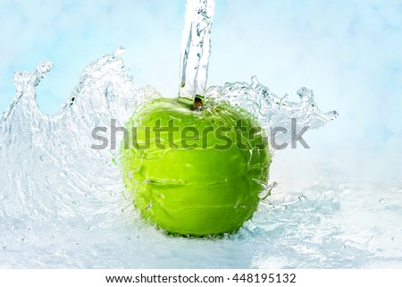 green apple while being washed with water