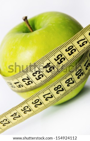 green apple with a measure tape close up - stock photo