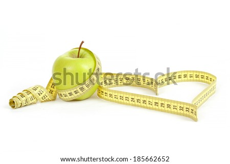 green apple with a measuring tape and heart symbol isolated on white background  - stock photo