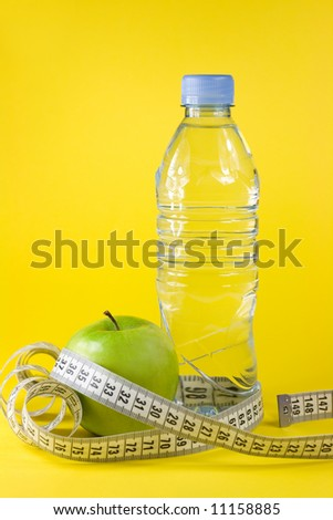 Green apple with centimeter and bottle on yellow background - stock photo