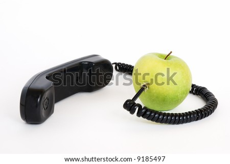 Green apple with handset and connected wire isolated on white