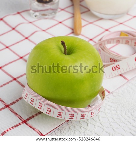 Green apple with measure tape and diet symbol concept on white background, close up, selective focus.