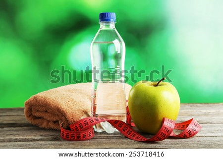 Green apple with measuring tape and bottle of water on grey wooden background - stock photo