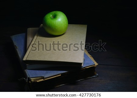 Green apple with old books on black wood background, dark tone.