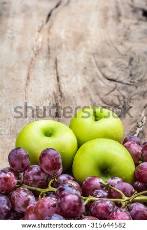 green apple with red grape on old wooden table