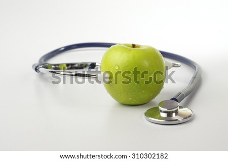 Green apple with stethoscope and measurement tape - stock photo