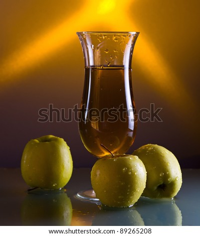 green apples and glass with juice on a glass table.