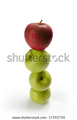 Green apples balanced on top of one another with a red apple on top with moisture - stock photo