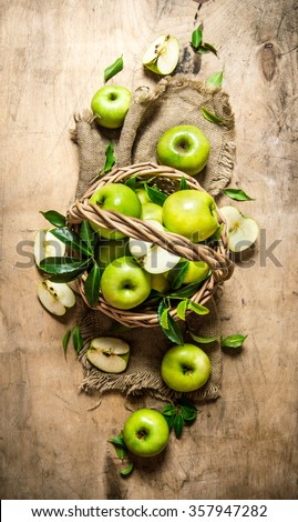 Green apples in an old basket. On a wooden table. Top view - stock photo