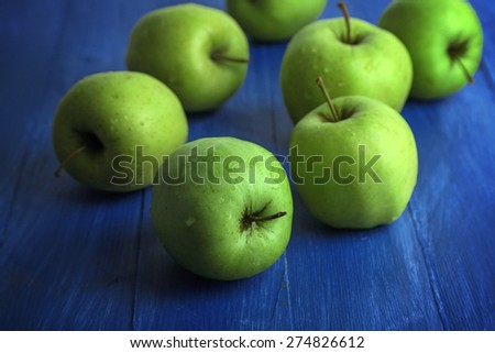 Green apples on color wooden background - stock photo