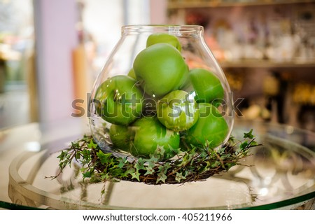 Green apples on table in glass vase