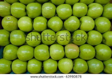 Green apples stacked together on farm stand - stock photo