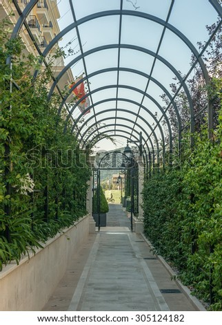 green arcs made of tropical plants above pedestrian pathway. - stock photo