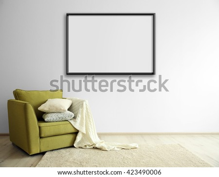 Green armchair and empty picture frame on light wall background - stock photo