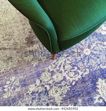 Green armchair on blue retro style carpet. Stylish furniture.