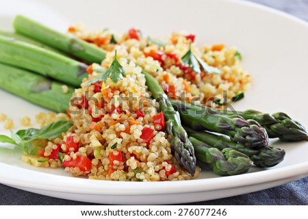 Green asparagus and quinoa salad with vegetables mix,lemon and parsley. Selective focus. - stock photo