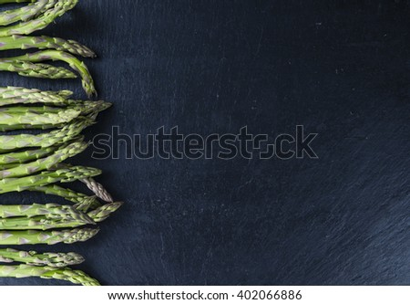 Green Asparagus (close-up shot) on a slate slab (selective focus) - stock photo