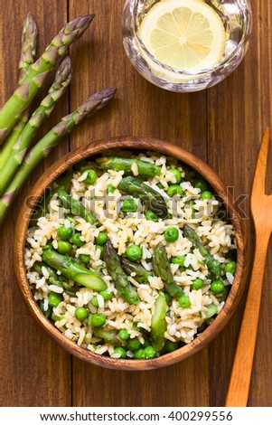 Green asparagus, pea, parsley and brown rice risotto served in wooden bowl, photographed overhead on dark wood with natural light