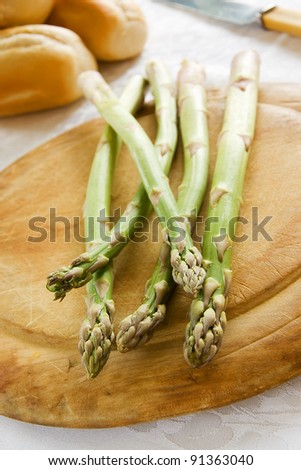Green asparagus spears on a wooden chopping board - stock photo
