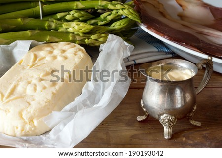 green Asparagus with Butter, Sauce Hollandaise and Ham on a wooden Table