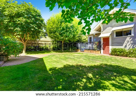Green backayrd garden with brick tile walkway. House with wooden deck - stock photo
