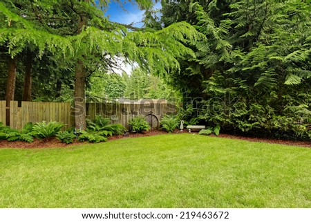 Green backyard area with wooden fence and decoration - stock photo