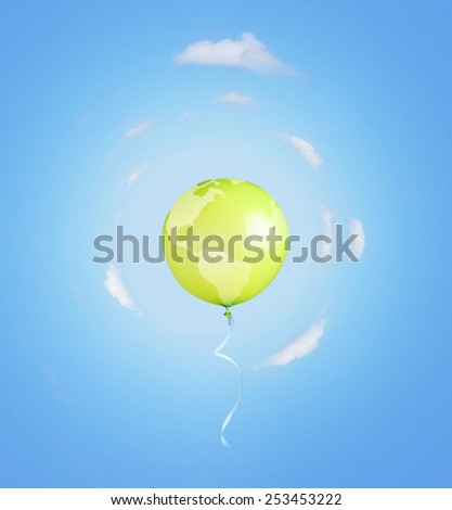 Green balloon like earth planet with ribbon flying into the sky. - stock photo