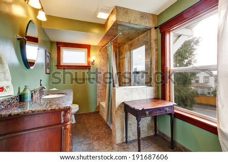 Green bathroom with tile floor and tile wall trim behind tub - stock photo