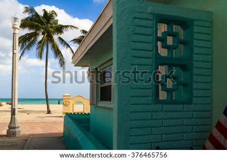 Green beach house and palm tree - stock photo