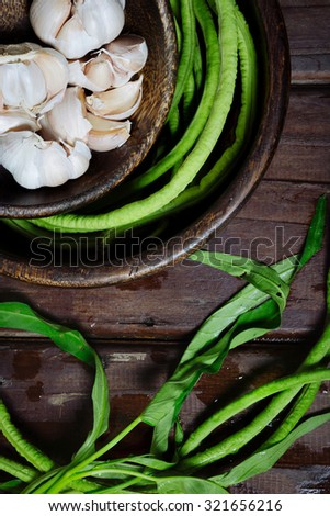 Green beans and garlic in wooden bowls on the rustic table. Vegetarian food
