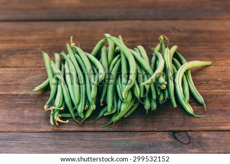 Green beans in a bowl on wooden background in rustic style - stock photo