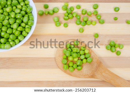 Green beans peas in wooden spoon on the background of scattered peas